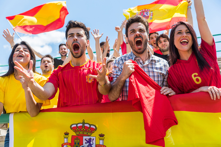 Spanish supporters cheering at stadium with flags. Group of fans watching a match and cheering team Spain. Sport and lifestyle concepts.