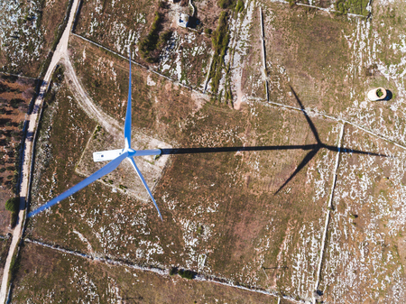 Wind turbine and shadow aerial view from the top. Electrical energy generation from wind for environmental protection