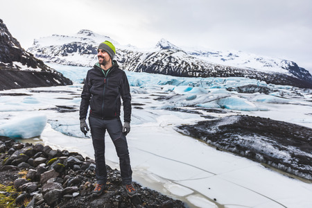 Man and adventurer portrait with glacier on background in Iceland. Man standing in front of a beautiful scene with ice and icebergs in the lagoon. Travel, nature and adventure concepts