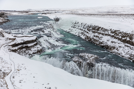 Gullfoss waterfall, Iceland, with snow in winter. Dramatic landscape of this majestic waterfall in the Icelandic Golden circle. Travel and nature concepts.
