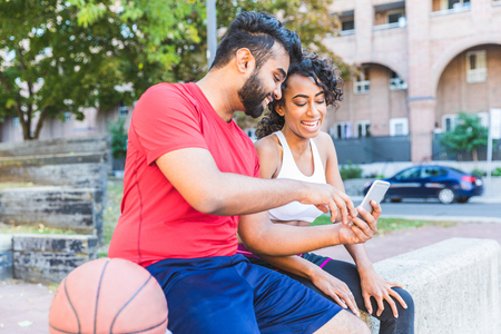 Black couple with phone and basketball at park. Young man and woman sitting on a concrete wall, looking at smartphone and smiling. Sport and lifestyle concepts Фото со стока