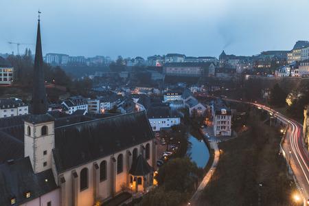De stadspanorama van Luxemburg bij schemer in de winter, met rook die uit schoorstenen en lage wolken komt. Architectuur en reisconcepten Stockfoto - 90237648