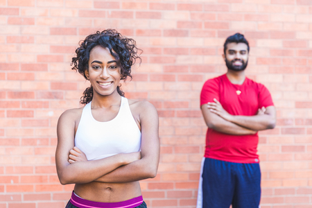 Sport black woman and man portrait. Young couple standing and looking at camera, smiling, after a work out session. Sport and healthy lifestyle concepts
