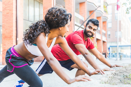 Black woman and man doing stretching exercises. Young couple training and looking at each other, focused, during a workout session. Sport and healthy lifestyle concepts Фото со стока