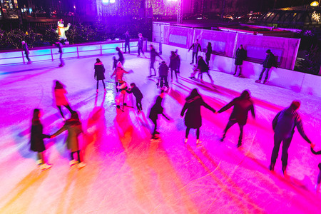 クリスマス休暇中にミュンヘンでスケートを人します。アイス スケート リンクと遊んで楽しいぼやけた人は認識できません。祝日とレジャーの概念