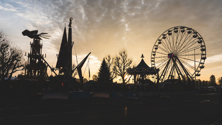 Fun fair silhouette at sunset. Panoramic view of an amusement park with ferris wheel. Dramatic sky on background. Stock Photo