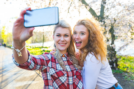 Two women taking a selfie at park in London. Two beautiful girls, lesbian couple or friends, having fun and bonding together on a sunny day. Homosexuality and lifestyle concepts.