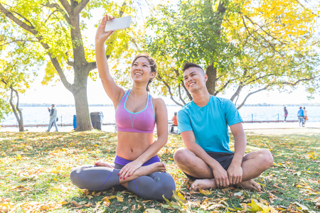 Chinese couple taking a selfie after yoga session in Toronto. Asian man and woman with legs crossed, sitting on the ground at park. Stress and relax related to yoga
