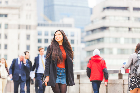 Beautiful Chinese woman walking in London on a sunny spring day. Asian girl wearing smart casual clothes with a denim skirt and grey coat.