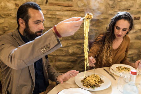 People eating tagliatelle pasta, lunch at Italian restaurant . Two persons, a woman and a man sitting at the table and enjoying food together. Italian style and food in old fashioned restaurant