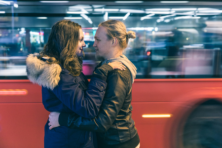 Happy couple embracing with a blurred red bus on background. Man and woman looking each other, side view, next to a busy road in London. Travel and love concepts