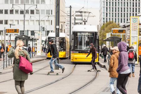 ベルリン、ドイツ - 2016年4月23日:黄色のトラムと人々、歩行者やスケーターで、通りを横断する忙しいアレクサンダー広場。アレクサンダー広場は、
