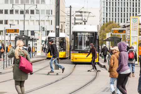 BERLIN, GERMANY - APRIL 23, 2016: Busy Alexanderplatz, with yellow tram and people, pedestrians and skaters, crossing the street. Alexanderplatz is the main square in East Berlin.