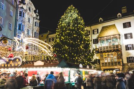 夜のインスブルックのクリスマスマーケットと木。ぼやけた人々、ライトの装飾、有名な金色の屋根と大きな木との長時間露光画像。休日とお祝い