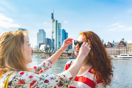 Girls friends having fun in Frankfurt on a sunny day. Women together outdoors, wearing sunglasses and walking on riverside promenade. Friendship and travel concepts