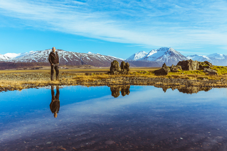 Man explorer in Iceland with his reflection on the water. Adult man walking and looking around. Majestic mountains on background, reflections on water on foreground. Travel and wanderlust concept Stock Photo