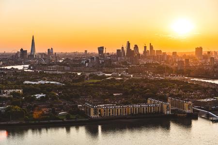 Londen skyline luchtfoto bij zonsondergang. Panorama van de wolkenkrabbers en huizen van Londen met de zon die op achtergrond plaatst. Reis- en architectuurconcepten