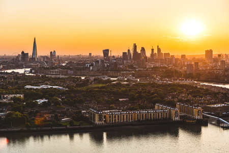 London skyline aerial view at sunset. Panoramic view of London skyscrapers and houses with the sun setting on background. Travel and architecture concepts