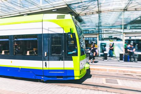 駅に近づくか、駅を出るぼやけたトラム。都会のシーン、公共交通機関モード、プラットフォームで待っている人々。都市生活、通勤、交通の概念