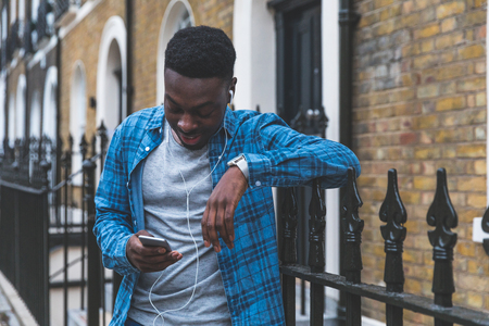 Black man listening music with phone in London. Young man wearing a checked shirt, holding a smart phone and wearing white earphones. Lifestyle and relax concepts Reklamní fotografie