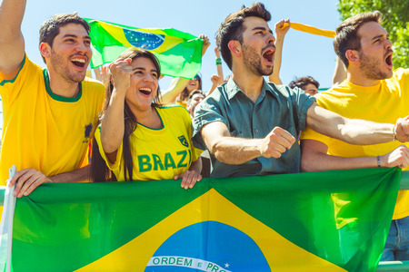 Brazilian supporters celebrating at stadium with flags. Group of fans watching a match and cheering team Brazil. Sport and lifestyle concepts. 스톡 콘텐츠