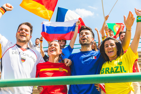 Happy supporters from different countries together at stadium. Fans from France, Germany, Spain, Brazil and other countries enjoying a match together. Sport, respect and fair play concepts