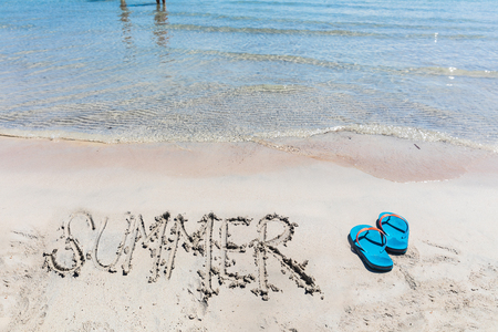 Summer writing on the sand at seaside with flip flops. Travel and lifestyle concepts with summer and holidays . Empty space to add text on the top of the photo.
