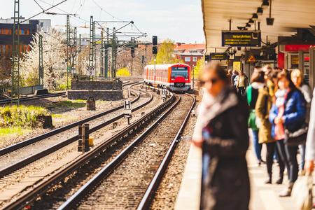 기차역에서 플랫폼에서 기다리는 사람들. 함부르크에서 붐비는 기차역을 기다리는 관광객과 통근자가있는 역. 여행 및 라이프 스타일 개념