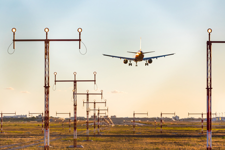 Airplane landing at sunset, rear view with approach lighting system.