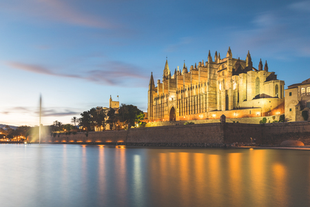 Palma de Majorca cathedral at dusk. Beautiful view of the impressive church with a lake and fountain on foreground and blurred clouds in the sky. Travel and architecture concepts. Stock Photo