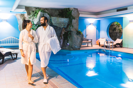 Couple in relax at therme with swimming pool. Man and woman wearing batrobe enjoying time at spa. Leisure and luxury relax concepts