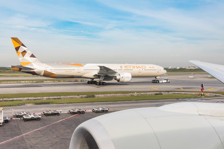 BANGKOK, THAILAND - NOVEMBER 28, 2017: Etihad Boeing 777 on taxiway at Suvarnabhumi airport pulled by a tug to departing position. View from over wing seat on a Boeing 777, B777.