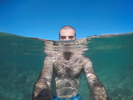 Man taking a selfie part underwater at seaside in Spain. Young man holding an action camera half underwater and half emerged showing both scenarios at once. Travel and leisure concepts