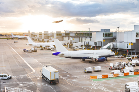 Busy airport view with airplanes and service vehicles at sunset
