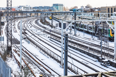 Rail tracks aerial view and trains covered by snow in London. UK capital city covered by snow after a powerful snowstorm. Travel and weather concepts related. Imagens