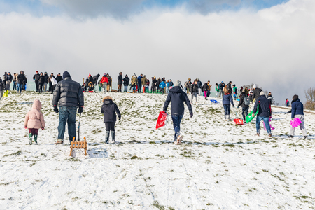 LONDON, UK - FEBRUARY 28, 2018: Many persons, adults and children, having fun on the snow at Primrose hill with sledges and playing snowballs fight.