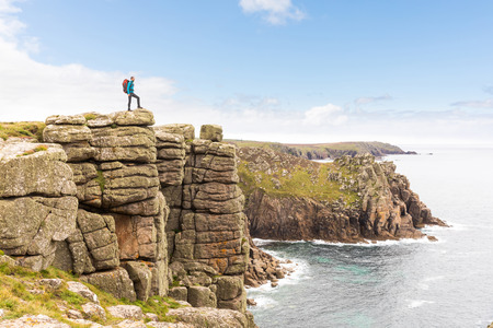 Man standing on a rock cliff enjoying the view. Young man with backpack and hiking clothes on the cliffs over seashore in Cornwall, UK. Travel, nature and wanderlust concepts. Imagens
