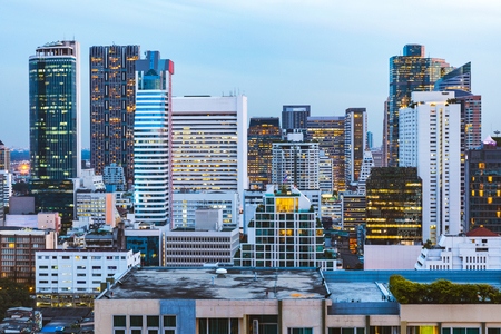 Modern buildings and skyscrapers in Bangkok at dusk. Cityscape in the capital city of Thailand after sunset with lights switched on. Architecture and travel. Banco de Imagens