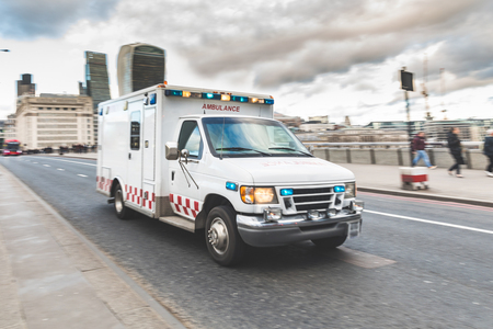 Emergency ambulance rushing on the street with emergency lights flashing in London city centre. Medical and emergency concepts, panning technique.