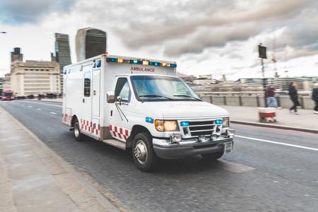Rettungswagen, der auf die Straße mit den Notlichtern blinken im London-Stadtzentrum hetzt. Medizinische und Notfallkonzepte, Schwenktechnik. Standard-Bild