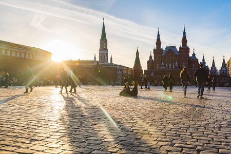 MOSCOW, RUSSIA - APRIL 9, 2018: People, tourists, in the Red Square at sunset. Kremlin building on the left and the State Historical Museum on the right. Travel and architecture are the main concepts