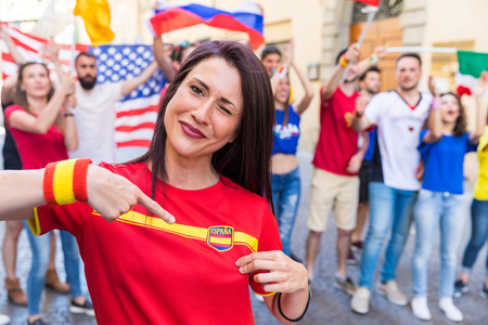 Spanish woman supporter celebrating victory of team Spain, and fans from other countries enjoying sport together during international tournament. Sport, respect and fair play concepts