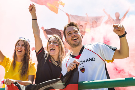 German supporters celebrating at stadium for football match. Group of fans and friends watching a match and cheering team Germany for international competition. Sport and lifestyle concepts.