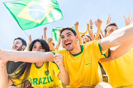 Brazilian supporters celebrating at stadium with flags. Group of fans and friends watching a match and cheering team Brazil. Sport and lifestyle concepts during international cup match