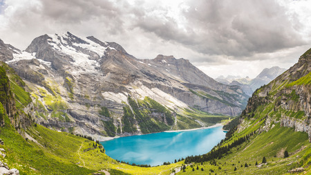 Oeschinen Lake panoramic view in the Swiss alps with beautiful turquoise water. Clouds in the sky before a storm. Mountains with glacier and snow all around. Nature and travel concepts