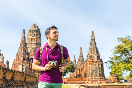 Tourist in Ayutthaya, Thailand, at historical park with ruins. Young man on summer holidays enjoying a sunny day, taking photos with vintage camera. Travel and tourism concepts.