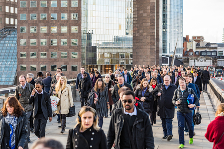 LONDON, UK - MARCH 16, 2018: Crowd of commuters and tourists walking on London Bridge during morning rush hour. The bridge connects London Bridge station to the city.