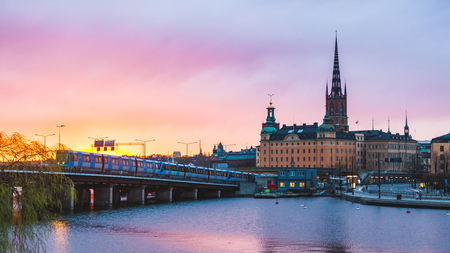 View of Stockholm old town and metro train at sunset. Typical scandinavian architecture and colors with pink and orange clouds. Travel and tourism concept in the capital city of Sweden. Standard-Bild
