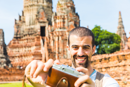 Tourist in Ayutthaya, ancient capital of Thailand, taking a selfie with vintage camera. Old ruins of temples on background at historical park on a sunny day. Tourism and travel concepts.