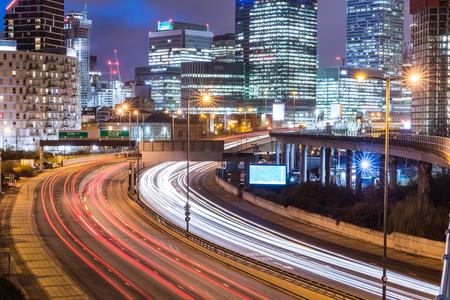 Nacht uitzicht op de stad met wolkenkrabbers en verkeerslichtpaden. De stedelijke scène van Londen in Canary Wharf met drukke weg en lichten van het financiële district op achtergrond. Reis- en architectuurconcepten